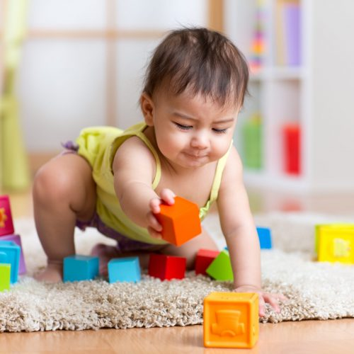 baby toddler playing  wooden toys at home or nursery