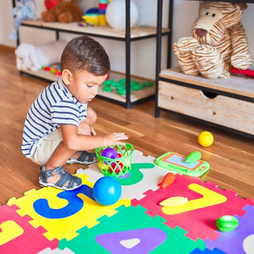 Beautiful toddler boy sitting on puzzle playing meals with plastic plates, fruits and vegetables at kindergarten